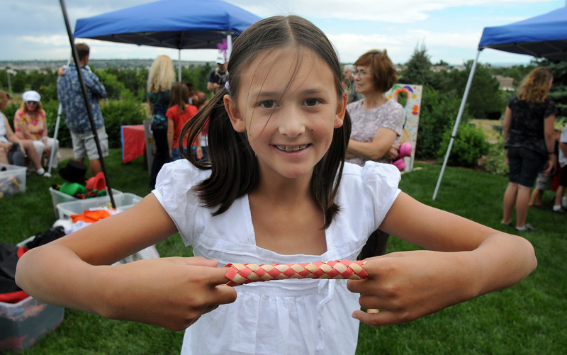 Emiko Boyer, 10, demonstrates her finger puzzle during the Broomfield Council on the Arts and Humanities Summer Sundays at the Brunner <br /> Farmhouse.<br /> <br /> July 11, 2010<br /> Staff photo/ David R. Jennings