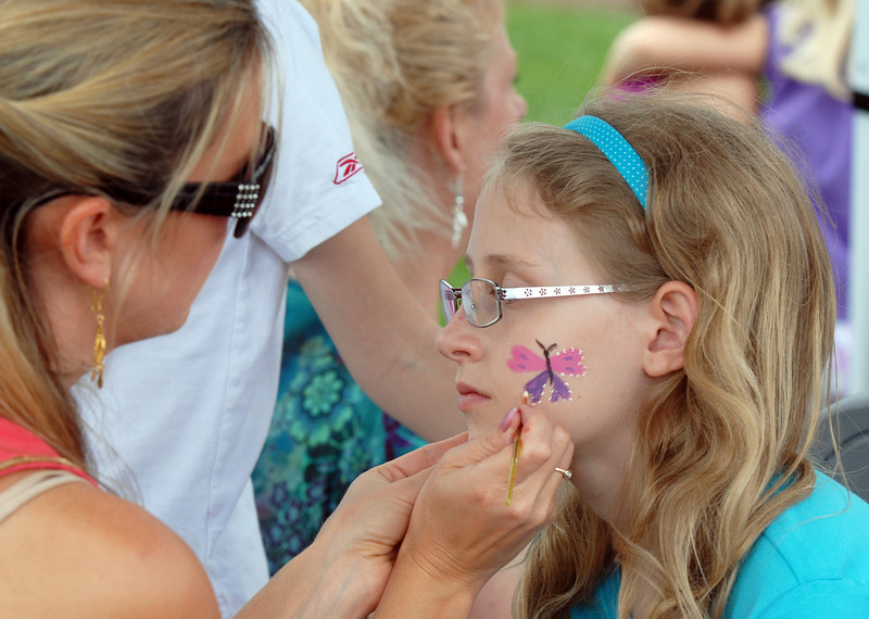 Brooke Nordgren, left, paints a butterfly on the cheek of Brittney Geurink, 11, during the Broomfield Council on the Arts and Humanities Summer Sundays at the Brunner <br /> Farmhouse.<br /> <br /> July 11, 2010<br /> Staff photo/ David R. Jennings