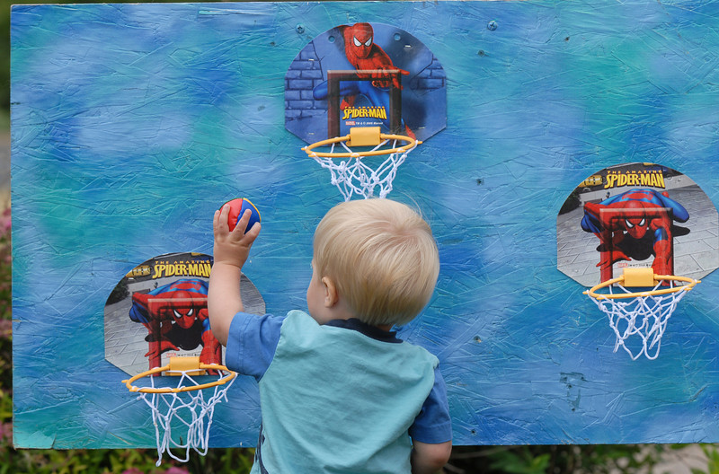 Finn Lasker, 1, tries his best to put a ball in the hoops during the Broomfield Council on the Arts and Humanities Summer Sundays at the Brunner <br /> Farmhouse.<br /> <br /> July 11, 2010<br /> Staff photo/ David R. Jennings
