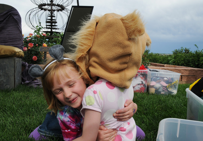 Julia Kirk, 7, left, gives her sister Emily , 5, a hug at the end of the play lion and the mouse in the Backstory Theater Academy booth during the Broomfield Council on the Arts and Humanities Summer Sundays at the Brunner <br /> Farmhouse.<br /> <br /> July 11, 2010<br /> Staff photo/ David R. Jennings