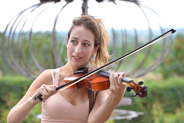 Angie Farrell gives playing a violin a try during Summer Sundays at the Brunner Farmhouse on Sunday.<br /> <br /> July 8, 2012<br /> staff photo/ David R. Jennings