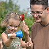 Stella High, 2, left, listens to her bell along with the bell her father Chris is ringing during Summer Sundays at the Brunner Farmhouse on Sunday.<br /> <br /> <br /> July 8, 2012<br /> staff photo/ David R. Jennings