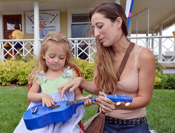 Angie Farrell, right, helps her daughter Kayla Farrell-Herrick, 2, play a ukulele during Summer Sundays at the Brunner Farmhouse on Sunday.<br /> <br /> July 8, 2012<br /> staff photo/ David R. Jennings