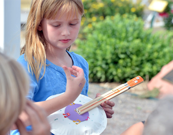 Julia Kirk, 9, strums her paper plate banjo during Summer Sundays at the Brunner Farmhouse on Sunday.<br /> <br /> July 8, 2012<br /> staff photo/ David R. Jennings