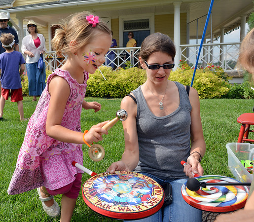 Myra High, 4, left, hits a drum held by her mother Sarah during Summer Sundays at the Brunner Farmhouse on Sunday.<br /> <br /> July 8, 2012<br /> staff photo/ David R. Jennings