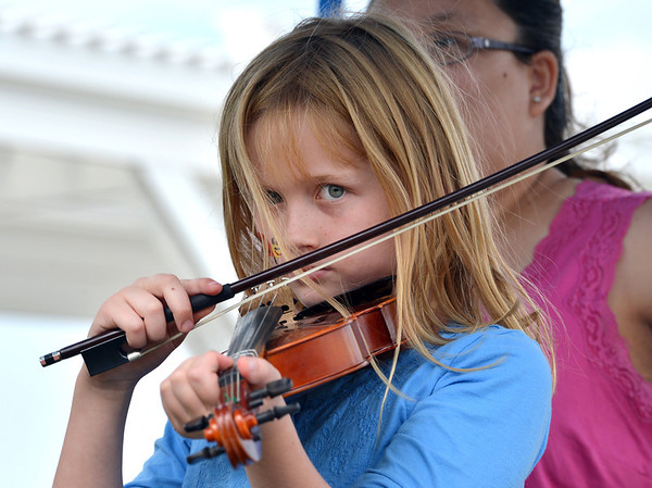 Julia Kirk, 9, gives playing a violin a try during Summer Sundays at the Brunner Farmhouse on Sunday.<br /> <br /> July 8, 2012<br /> staff photo/ David R. Jennings