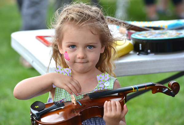 Kayla Farrell-Herrick, 2, plucks the violin during Summer Sundays at the Brunner Farmhouse on Sunday.<br /> <br /> July 8, 2012<br /> staff photo/ David R. Jennings