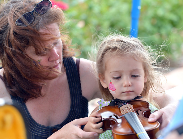 Kayla Farrell-Herrick, 2, gets a little help with playing the violin from Morag Barrett during Summer Sundays at the Brunner Farmhouse on Sunday.<br /> <br /> July 8, 2012<br /> staff photo/ David R. Jennings