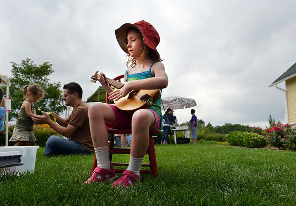 Emily Kirk, 7, strums a mandolin during Summer Sundays at the Brunner Farmhouse on Sunday.<br /> <br /> July 8, 2012<br /> staff photo/ David R. Jennings