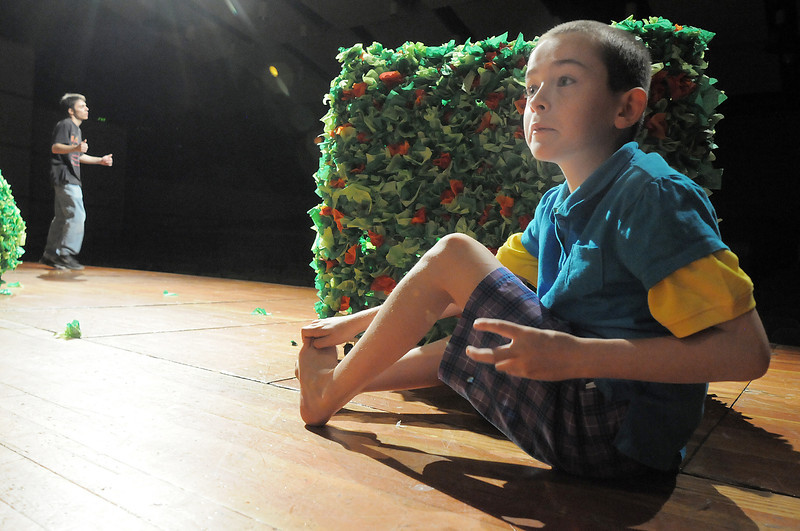 Noah Tibbetts, 9, one of the Munchkins hides behind a bush during the Summer Youth Players tech rehearsal of The Wizard of Oz at Broomfield High School on Saturday.<br /> June 18, 2011<br /> staff photo/David R. Jennings