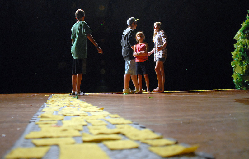 Megan Martin, 11, right, Dorothy, Hadley Pancratz, 7, Beau Clayton, Cowardly Lion, and Bryce Wilcox, 13, The Tin Man, walk on the yellow brick road during the Summer Youth Players tech rehearsal of The Wizard of Oz at Broomfield High School on Saturday.<br /> June 18, 2011<br /> staff photo/David R. Jennings