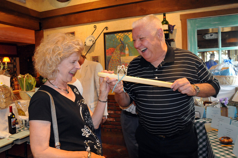 Doris Sauerland, left, and Paul Williams joke while looking at a flute for the silent auction during Summer Night at Mimi's benefit for Broomfield Senior Services at Mimi's Cafe on Wednesday<br /> August 18, 2010<br /> staff photo/David R. Jennings