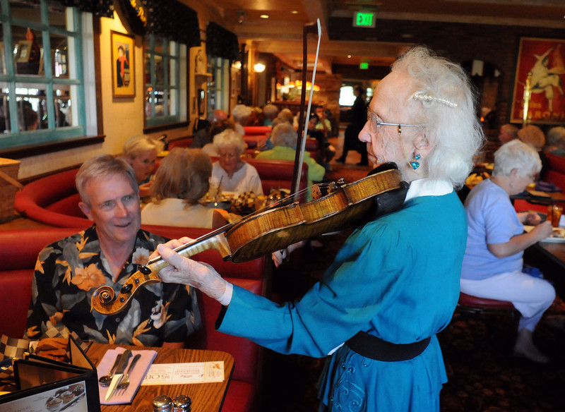 Violinist Lucille Weed, 85, serenades Steve Larson during Summer Night at Mimi's benefit for Broomfield Senior Services at Mimi's Cafe on Wednesday.<br /> August 18, 2010<br /> staff photo/David R. Jennings