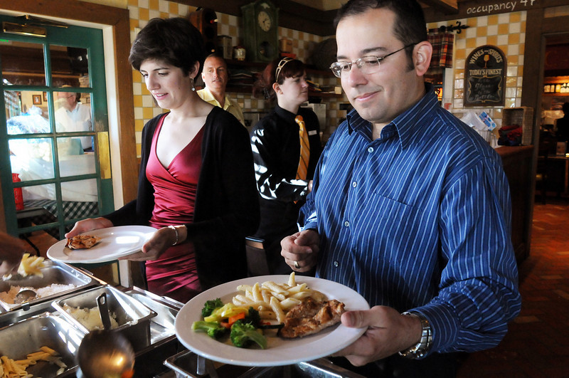 Nicholas Kawalec, right, and Andrea Balazs are served at the buffet table during Summer Night at Mimi's benefit for Broomfield Senior Services at Mimi's Cafe on Wednesday<br /> August 18, 2010<br /> staff photo/David R. Jennings