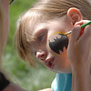 Samantha Labriola, 5, has a Batman symbol painting on to her cheek by Brooke Nordgren during Summer Sundays at the Brunner Farmhouse sponsored by the Broomfield Council on the Arts and Humanities on Sunday.<br /> <br /> August 7, 2011<br /> staff photo/ David R. Jennings