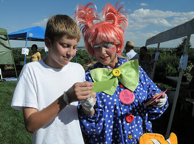 Bryce Wilcox, 14, left, reads a joke card with Thilly the clown, Cindy Card, during Summer Sundays at the Brunner Farmhouse sponsored by the Broomfield Council on the Arts and Humanities on Sunday.  August 7, 2011 staff photo/ David R. Jennings