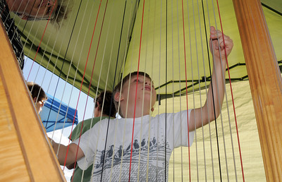 Conan Corcoran, 6, plucks the strings of Nancy Brace's harp duirng Summer Sundays at the Brunner Farmhouse sponsored by the Broomfield Council on the Arts and Humanities on Sunday.   August 7, 2011 staff photo/ David R. Jennings
