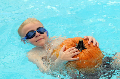 First grader Andrew Schoonveld carries a pumpkin in the water during the 4th annual swimming with pumpkins classes taught by Liz Kaplan at Broomfield Academy on Wednesday. October 19, 2011 staff photo/ David R. Jennings