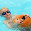 First grader Andrew Schoonveld carries a pumpkin in the water during the 4th annual swimming with pumpkins classes taught by Liz Kaplan at Broomfield Academy on Wednesday.<br /> October 19, 2011<br /> staff photo/ David R. Jennings