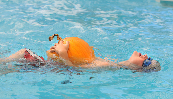 First grader Axel Bodeux carries a pumpkin while swimming during the 4th annual swimming with pumpkins classes taught by Liz Kaplan at Broomfield Academy on Wednesday. October 19, 2011 staff photo/ David R. Jennings