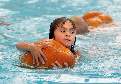 First grader Allie Bullen holds on to a pumpkin while swimming during the 4th annual swimming with pumpkins classes taught by Liz Kaplan at Broomfield Academy on Wednesday. October 19, 2011 staff photo/ David R. Jennings