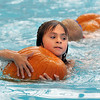 First grader Allie Bullen holds on to a pumpkin while swimming during the 4th annual swimming with pumpkins classes taught by Liz Kaplan at Broomfield Academy on Wednesday.<br /> October 19, 2011<br /> staff photo/ David R. Jennings