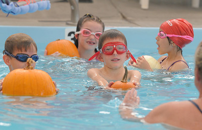 First graders Axel Bodeux, center, Brady Bowman, left, with Cadence Ames and Giovana Giorgetti during the 4th annual swimming with pumpkins classes taught by Liz Kaplan at Broomfield Academy on Wednesday. October 19, 2011 staff photo/ David R. Jennings