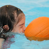 First grader Cadence Ames pushes a pumpkin by blowing bubbles during the 4th annual swimming with pumpkins classes taught by Liz Kaplan at Broomfield Academy on Wednesday.<br /> <br /> October 19, 2011<br /> staff photo/ David R. Jennings