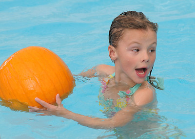 First grader Juliana Perez swims around the pool with her pumpkin during the 4th annual swimming with pumpkins classes taught by Liz Kaplan at Broomfield Academy on Wednesday.  October 19, 2011 staff photo/ David R. Jennings