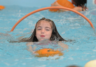 First grader Cadence Ames swims through a hoop leading with her pumpkin during the 4th annual swimming with pumpkins classes taught by Liz Kaplan at Broomfield Academy on Wednesday.  October 19, 2011 staff photo/ David R. Jennings