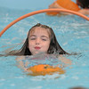 First grader Cadence Ames swims through a hoop leading with her pumpkin during the 4th annual swimming with pumpkins classes taught by Liz Kaplan at Broomfield Academy on Wednesday.<br /> <br /> October 19, 2011<br /> staff photo/ David R. Jennings