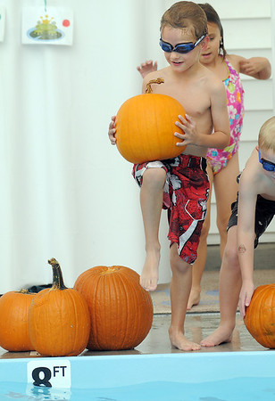 First grader Brady Bowman hoists a pumpkin to toss it in the pool  during the 4th annual swimming with pumpkins classes taught by Liz Kaplan at Broomfield Academy on Wednesday.<br /> <br /> October 19, 2011<br /> staff photo/ David R. Jennings