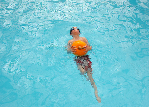 First grader Axel Bodeux pushes off of the pool carrying a pumpkin during the 4th annual swimming with pumpkins classes taught by Liz Kaplan at Broomfield Academy on Wednesday.<br /> <br /> October 19, 2011<br /> staff photo/ David R. Jennings