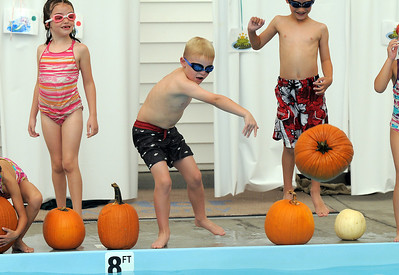 Andrew Schoonveld, center, tosses a pumpkin into the pool during the 4th annual swimming with pumpkins classes taught by Liz Kaplan at Broomfield Academy on Wednesday. October 19, 2011 staff photo/ David R. Jennings