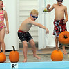 Andrew Schoonveld, center, tosses a pumpkin into the pool during the 4th annual swimming with pumpkins classes taught by Liz Kaplan at Broomfield Academy on Wednesday.<br /> October 19, 2011<br /> staff photo/ David R. Jennings