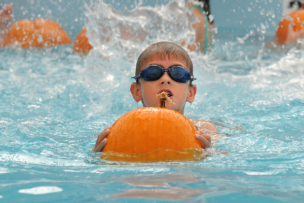 First grader Brady Bowman pushes a pumpkin while swimming during the 4th annual swimming with pumpkins classes taught by Liz Kaplan at Broomfield Academy on Wednesday.<br /> October 19, 2011<br /> staff photo/ David R. Jennings