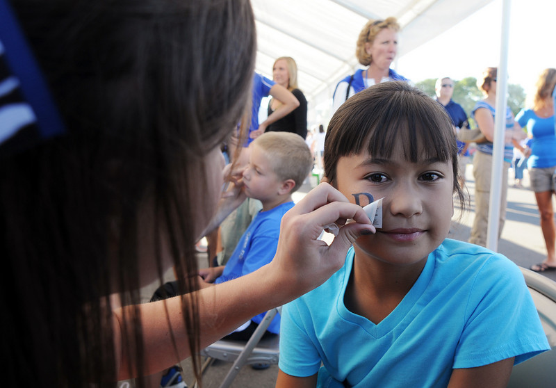 BE0919tail04<br /> Cassidy Azarcon, 7, has a tattoo put on by cheerleader Payton Landers at the tailgate party before Saturday's cross town game at Elizabeth Kennedy Stadium..<br /> <br /> September 11, 2010<br /> staff photo/David R. Jennings