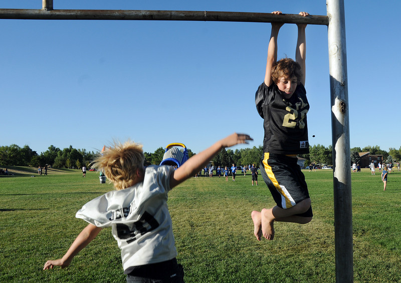 BE0919tail05<br /> Kaleb Foreman, 10, hangs from a goal post with his friend Noah Jenson, 10, at the tailgate party before Saturday's cross town game at Elizabeth Kennedy Stadium..<br /> <br /> September 11, 2010<br /> staff photo/David R. Jennings
