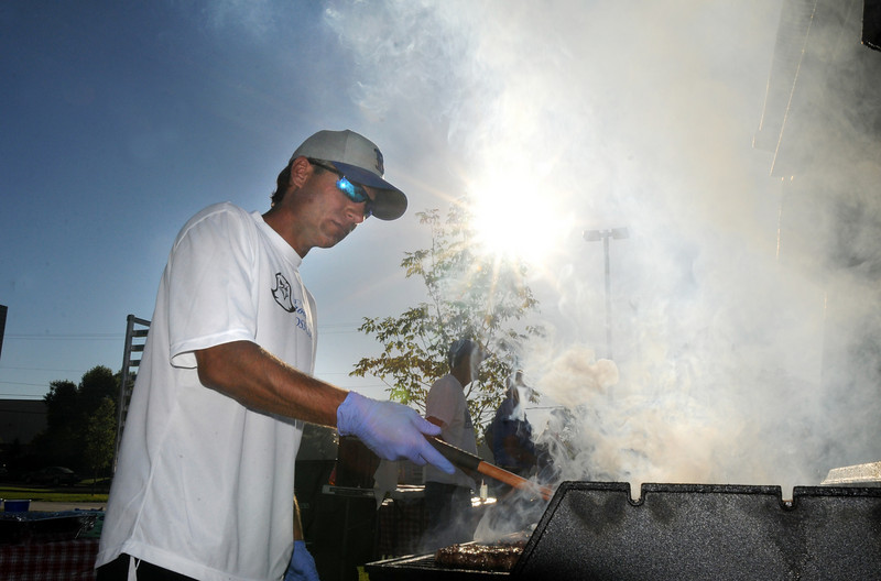 BE0919tail03<br /> Jason Sarno flips burgers at the tailgate party before Saturday's cross town game at Elizabeth Kennedy Stadium..<br /> <br /> September 11, 2010<br /> staff photo/David R. Jennings