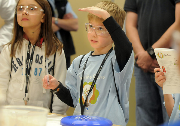 Griffin Waters, 7, center, tries to explain what might happen to milk to Job Donkor, quality control, while at the Mad Scientist station during take our Daughters and Sons to Work Day at White Wave Foods on Thursday.<br /> April 28, 2011<br /> staff photo/David R. Jennings