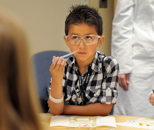 Raymond Rodriguez, 7, listens to the directions on how to add a base solution to milk in a petri dish during take our Daughters and Sons to Work Day at White Wave Foods on Thursday.<br /> April 28, 2011<br /> staff photo/David R. Jennings