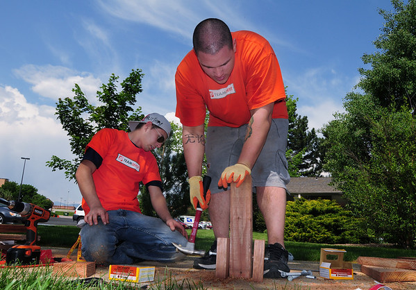 Home Depot employees Chris Lammey, left, and Tony Martinez build a bench to put around the tree at the entrance of the Broomfield Veterans Memorial Museum on Thursday. <br /> <br /> <br /> May 17, 2012 <br /> staff photo/ David R. Jennings