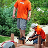 Home Depot employees Tony Martinez, left, stands on a support beam as Chris Lammey attaches screws as they build a bench to put around the tree at the entrance of the Broomfield Veterans Memorial Museum on Thursday. <br /> <br /> <br /> May 17, 2012 <br /> staff photo/ David R. Jennings
