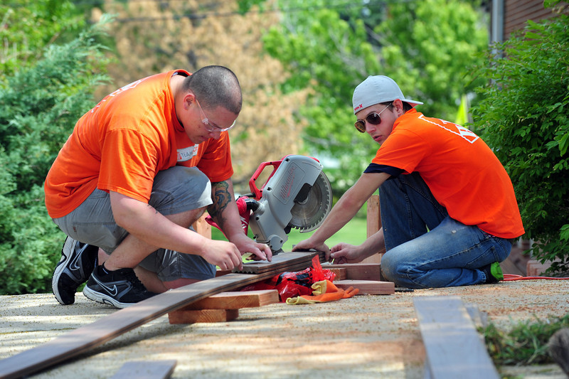 Home Depot employees Tony Martinez, left, and Chris Lammey build a bench to put around the tree at the entrance of the Broomfield Veterans Memorial Museum on Thursday. <br /> <br /> May 17, 2012 <br /> staff photo/ David R. Jennings