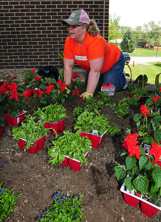 Home Depot employee Laura Green helps plant flowers at the entrance of the Broomfield Veterans Memorial Museum on Thursday. <br /> <br /> May 17, 2012 <br /> staff photo/ David R. Jennings