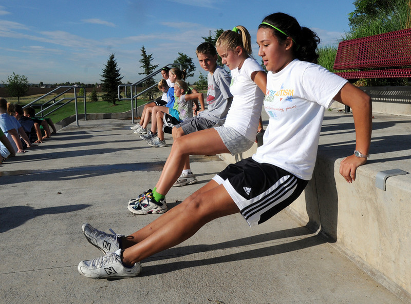 BE0725BOOT02<br /> Paige Jones, 15, right, and Madison Mueller, 11, with others does upper body exercises during the Teen Boot Camp at Broomfield County Commons Park on Thursday.<br /> July 22, 2010<br /> Staff photo/ David R. Jennings