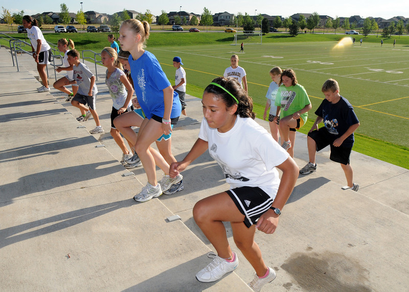 Lauren Jones, 15, right, does the stairs next to Rachel Himyak, 14, with the group during the Teen Boot Camp at Broomfield County Commons Park on Thursday.<br /> July 22, 2010<br /> Staff photo/ David R. Jennings