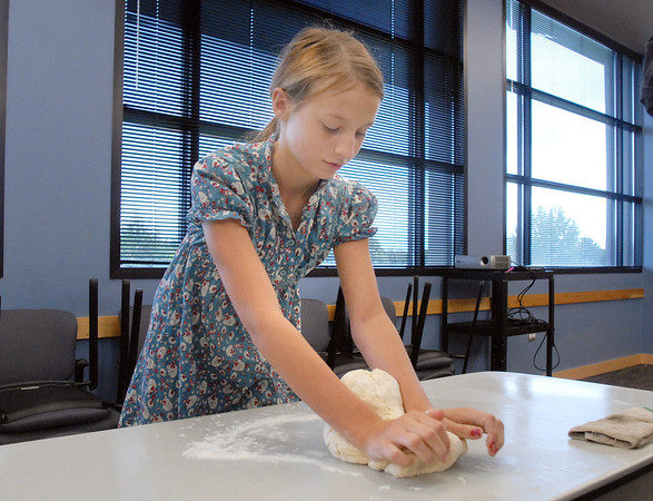 Layla Clark, 13, kneads brad dough during the teen cooking session of making Mediterranean dishes with at the Mamie Doud Eisenhower Public Library on Tuesday.<br /> <br /> July 5 2011<br /> staff photo/ David R. Jennings
