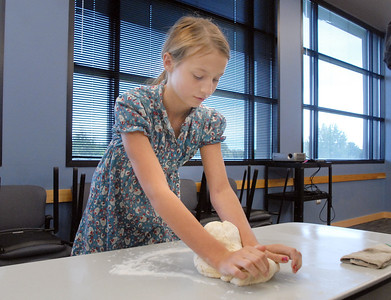 Layla Clark, 13, kneads brad dough during the teen cooking session of making Mediterranean dishes with at the Mamie Doud Eisenhower Public Library on Tuesday.  July 5 2011 staff photo/ David R. Jennings