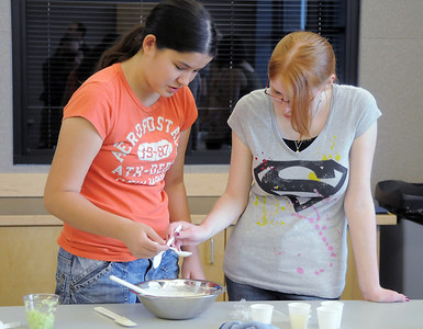 Camille Green, 13, left, and Michelle Bridenstine, 14, mix ingredients during the teen cooking session of making Mediterranean dishes with at the Mamie Doud Eisenhower Public Library on Tuesday.  July 5 2011 staff photo/ David R. Jennings